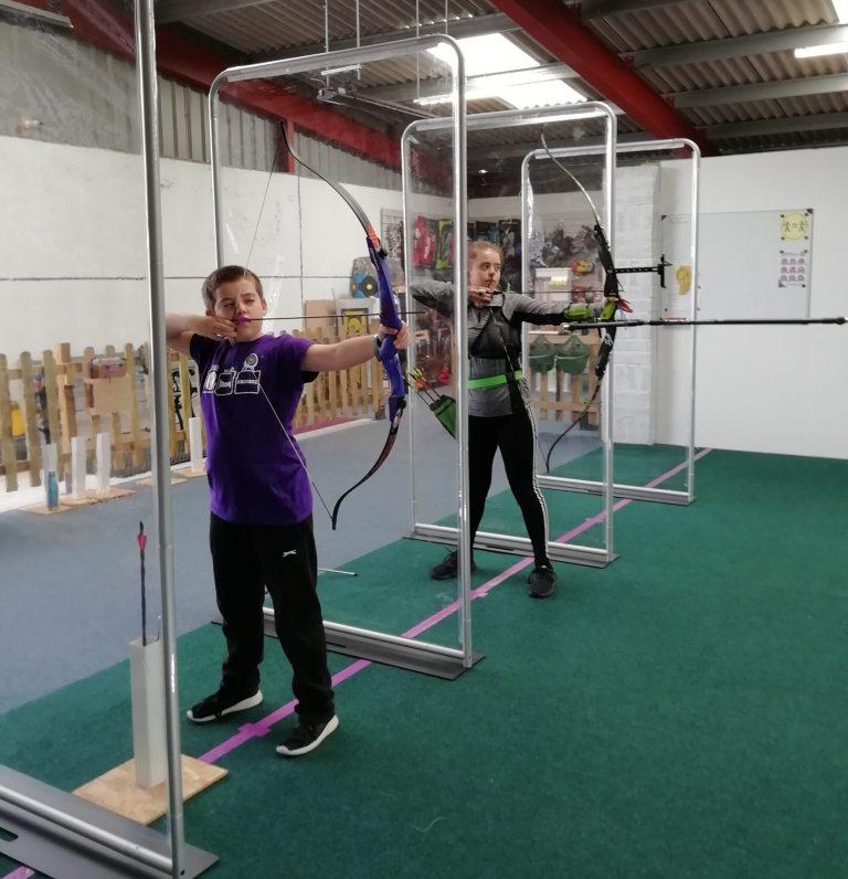 2 children shooting on the indoor range between clear screens